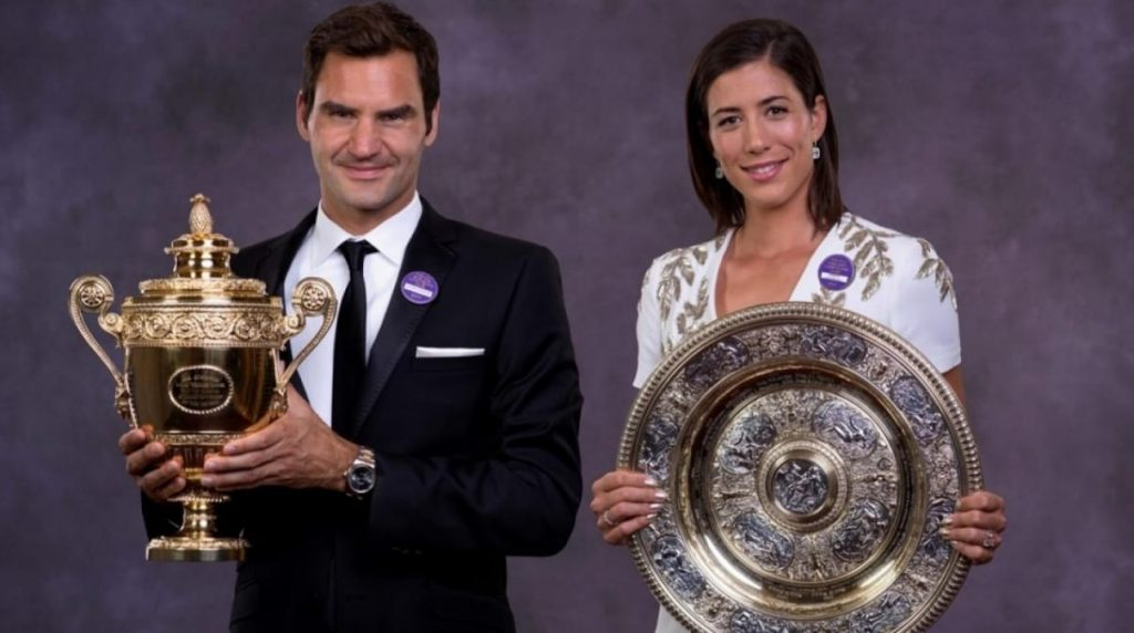 Garbine Muguruza and Roger Federer posing with their respective Wimbledon trophies in the Champions Dinner after the 2017 edition.