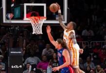 John Collins dunks on Kelly Olynyk during Hawks Pistons